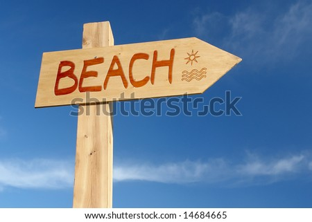 Wooden signpost indicating Beach direction over blue sky