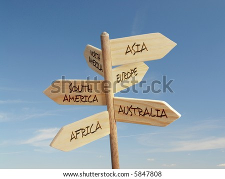 Wooden signpost indicating directions of six world continents over blue sky - stock photo