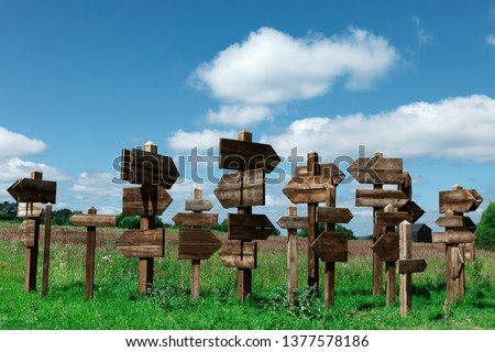Wooden signs indicating the direction in different directions to different directions. background: cloudy sky. #1377578186