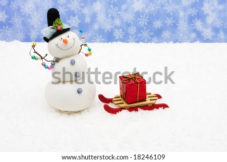Wooden sleigh sitting on snow with red Christmas present and snowman, winter fun