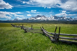 Wooden slit rail fence fades into the distance across a green and lush pasture toward the snow capped Sawtooth Mountain Range with a blue sky and white clouds above.