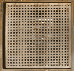 Wooden small square rattan wall panel. Style, design texture. perforated holes tiles with tracery. Close-up of interior design material for pattern background.