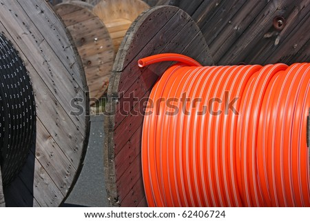 wooden spool with black and orange cables