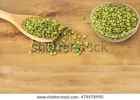 Wooden spoon and glass bowl with dry peas. #474478990
