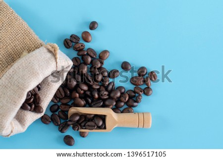 Wooden Spoon filled with coffee bean on blue background