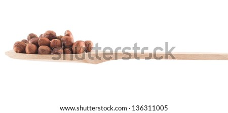 Wooden spoon full of hazelnuts isolated over white background, side view