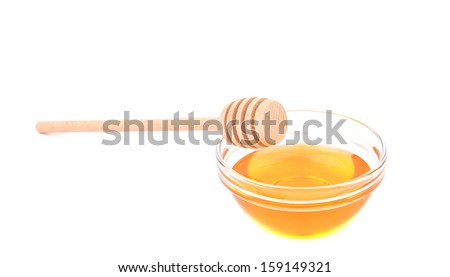 Wooden spoon on bowl with honey. Isolated on a white backgropund.
