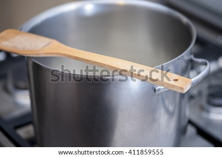 Wooden spoon over a hot metal pot while cooking a meal on a gas stove. Selecive focus.  #411859555
