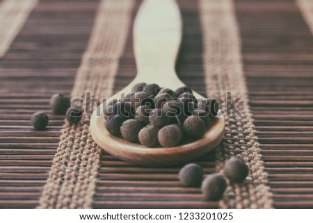 wooden spoon whole allspice closeup. background with allspice. #1233201025