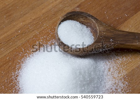 Wooden spoon with a pile of sugar or salt. Wooden surface.