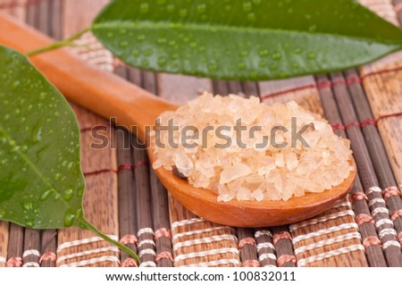 Wooden spoon with brown fragrant sea salt and wet leaves