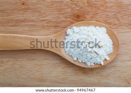 Wooden spoon with flour on a wooden table