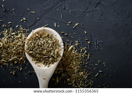 Wooden spoon with Italian seasoning-dried oregano with thyme,vegetables.Oregano in a wooden spoon on a rocky concrete dark black background with a place for text Top view  #1155356365