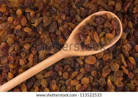 Wooden spoon with raisins is on raisins