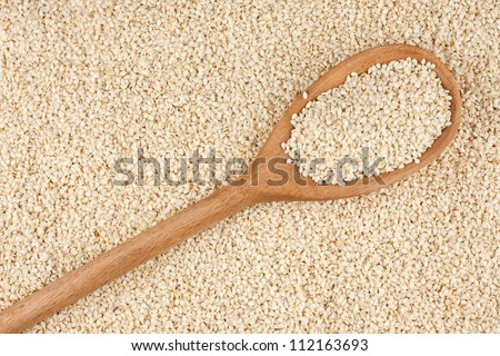 Wooden spoon with sesame seeds, sesame lies against