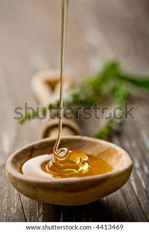 wooden spoon with wild honey falling into it