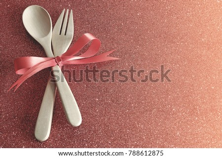 Wooden spoons and forks are strapped together with a bright red ribbon placed on a red gliiter background,dinner for lover in valentines day. #788612875