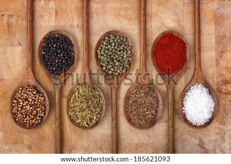 Wooden spoons full of aromatic herbs and spices on a wood cutting board