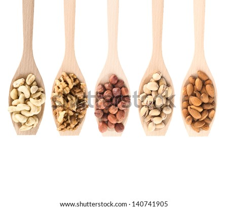 Wooden spoons full of different kinds of nuts: peanut, hazelnut, walnut, almond, pistachio, isolated over white background, top view