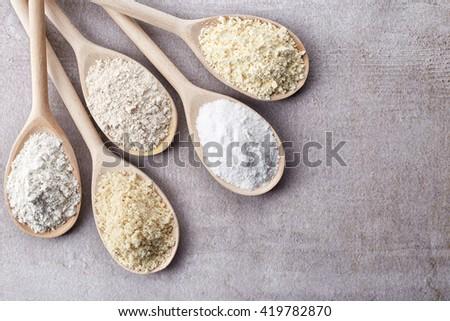 Wooden spoons of various gluten free flour (almond flour, amaranth seeds flour, buckwheat flour, rice flour, chick peas flour) from top view