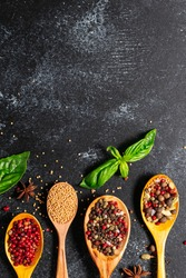 Wooden spoons with different aromatic organic spices on black wooden table with copy space for your text. Recipe book cover concept. Restaurant menu template.