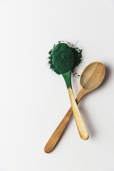 Wooden spoons with spirulina powder, superfood on a white background, vertical, full spoon