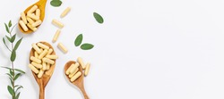 Wooden spoons with vegan vitamin capsules for immunity support and healthy lifestyle on white background with fresh green eucalyptus twig. Long banner format.