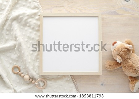 Wooden square frame mockup, empty frame mock up for nursery, baby room artwork, photo, sayings, flat lay composition with baby blanket, teddy bear and baby teether.