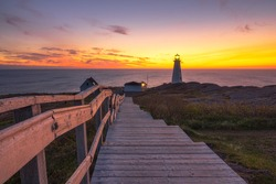 Wooden staircase and boardwalk at a beautiful sunrise, overlooking a white lighthouse sitting at the edge of a rocky cliff.  Cape Spear National Historic Site, St Johns Newfoundland.