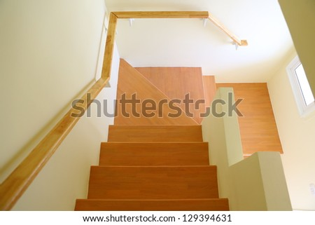 Wooden staircase and handrail leading to the upper, low level. Interior design.