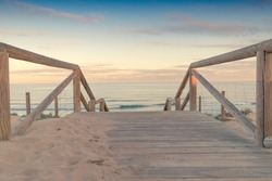 Wooden staircase and railing access to the beach sand at sunset with somewhat cloudy sky an sea with waves in Guardamar, Spain