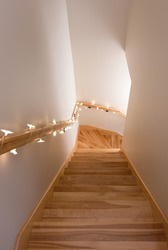 Wooden staircase decorated with cozy lights. Home interior.
