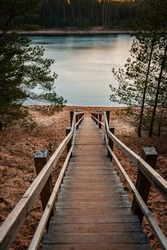 Wooden staircase leading to the Dubkalni Reservoir in Blue Hills of Ogre (Ogre Zilie Kalni). Nature Park with beautiful blue lake and pine forest. Latvia.