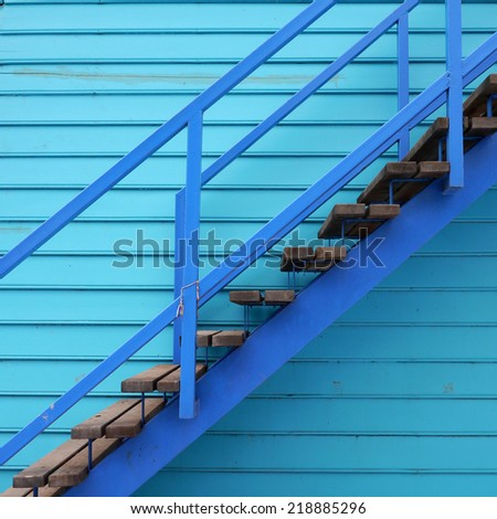 Wooden staircase on blue wooden background.