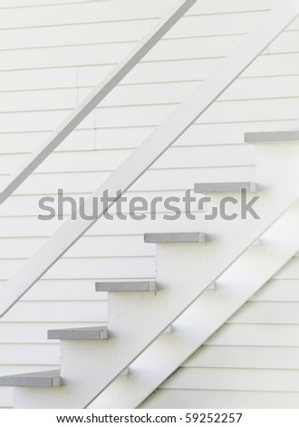 Wooden staircase on side of old-fashioned white wooden house