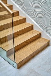 Wooden staircase with glass railings and wooden handrail of solid oak close view