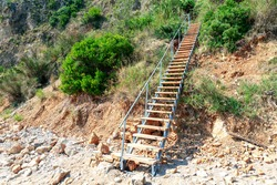 Wooden stairs descent to the beach . Coastal landslide