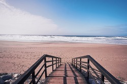 Wooden stairs heading down to the oceanbeach as sea foam and waves roll in. Portugal.