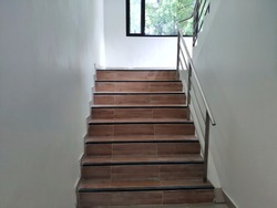 Wooden stairs in house with steel rail on the right.