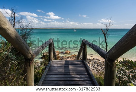 Wooden Stairs Leading to a Pristine Beach Paradise Overlooking a White Sail Boat and Mountains During a Beautiful Summer Day, Noosa National Park, Noosa Heads, Sunshine Coast, Queensland, Australia