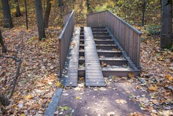 Wooden stairs with wheelchair ramp for bridge in park in autumn season