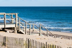 Wooden stairway leads to access of public/private beach, with dune protection fencing in foreground