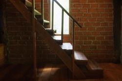 Wooden Stairway / staircase and handrail inside a dark rustic brick house.