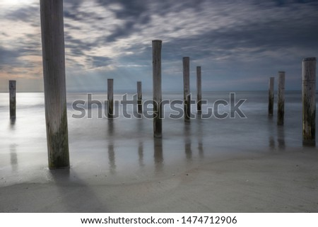 wooden stakes on sand holland beach during sunset #1474712906