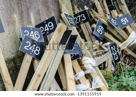 Wooden stakes with numbered signs to identify graves in a graveyard. #1391155919