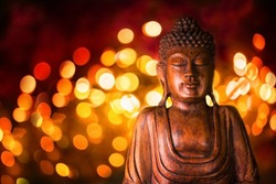 Wooden statue of Buddha  -  Symbol for Buddhism  -  Background with blurry bokeh lights