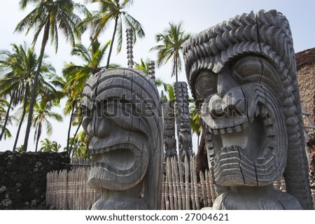 Wooden statues of idols standing next to old temple in Hawaii