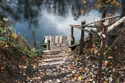 Wooden steps going down to the river in autumn forest. Lonely quiet fishing place