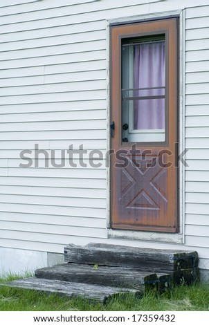 Wooden steps in front of a wooden door with a purple shade