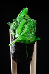 wooden sticks holding a green chukka roll on a black background close-up